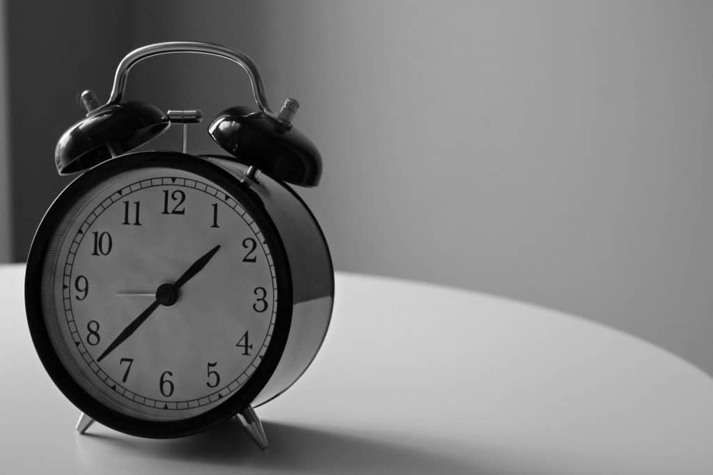 Black and white alarm clock on white table .  Wake up earlier