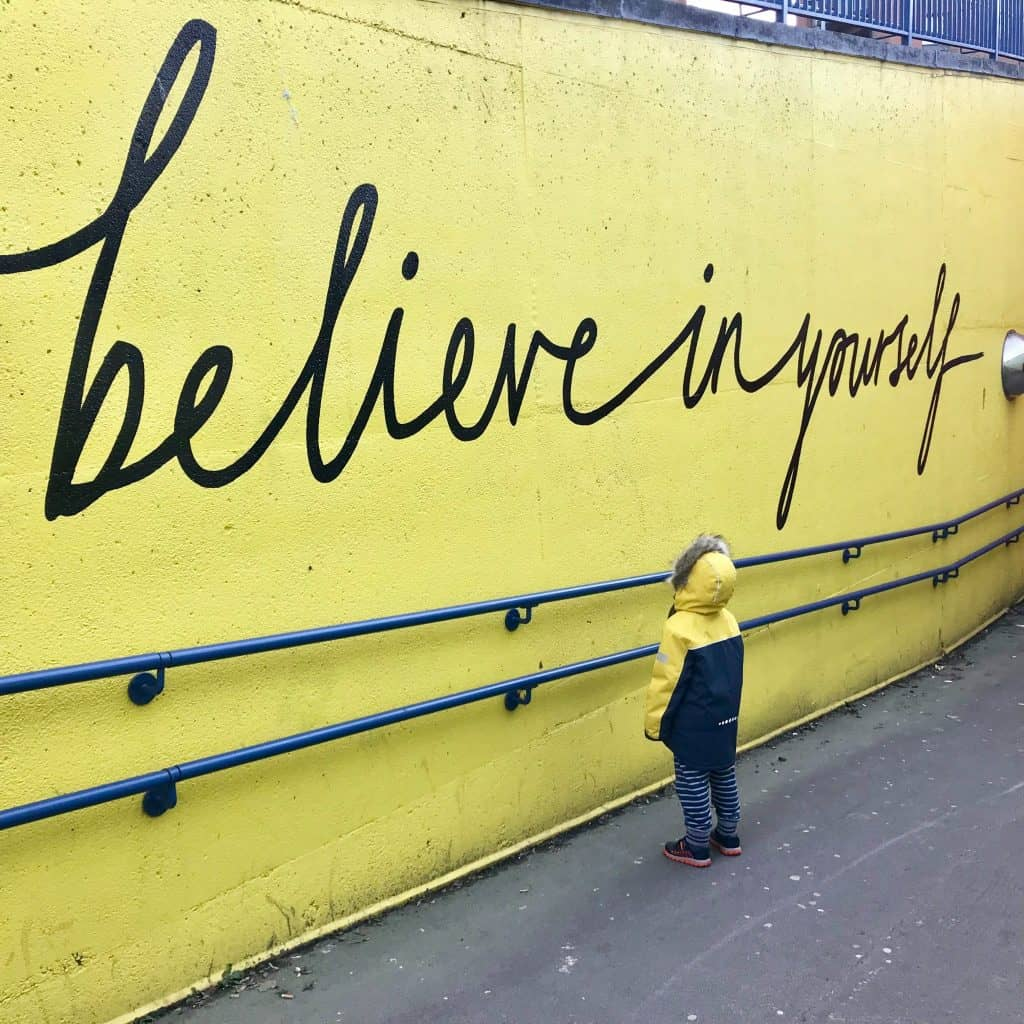 """Child looking at a mural saying """"believe in yourself"""" written in cursive on a yellow wall"""