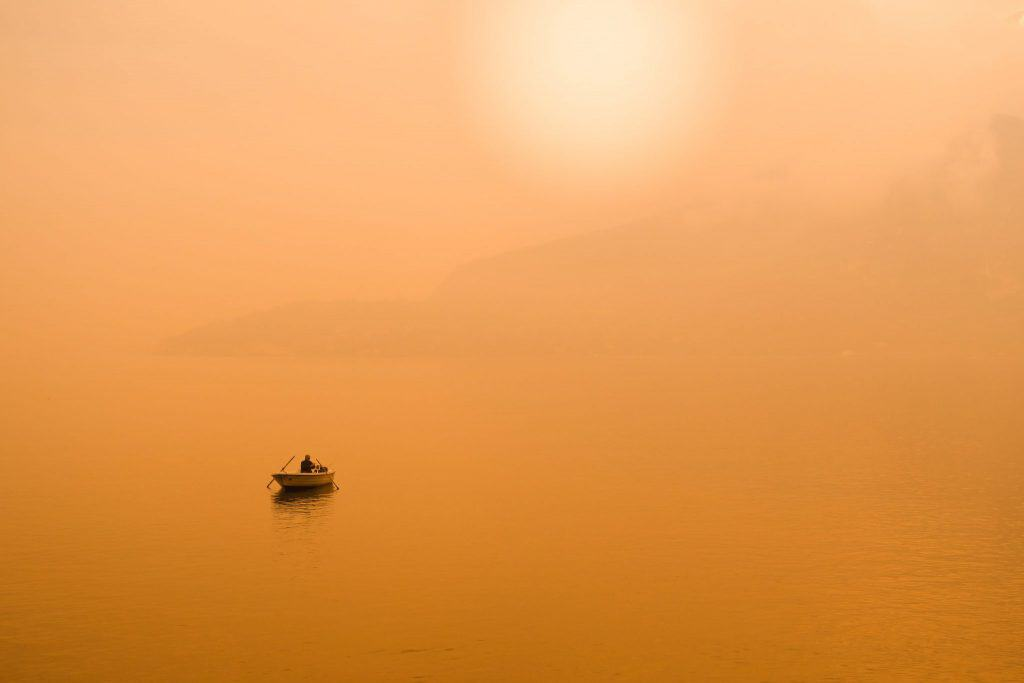 a man in a boat with an orange sky and orange water with the sun shining through the haze