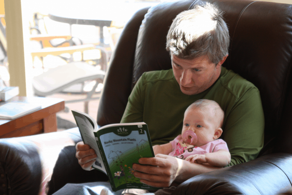 SAHD reading to baby in chair